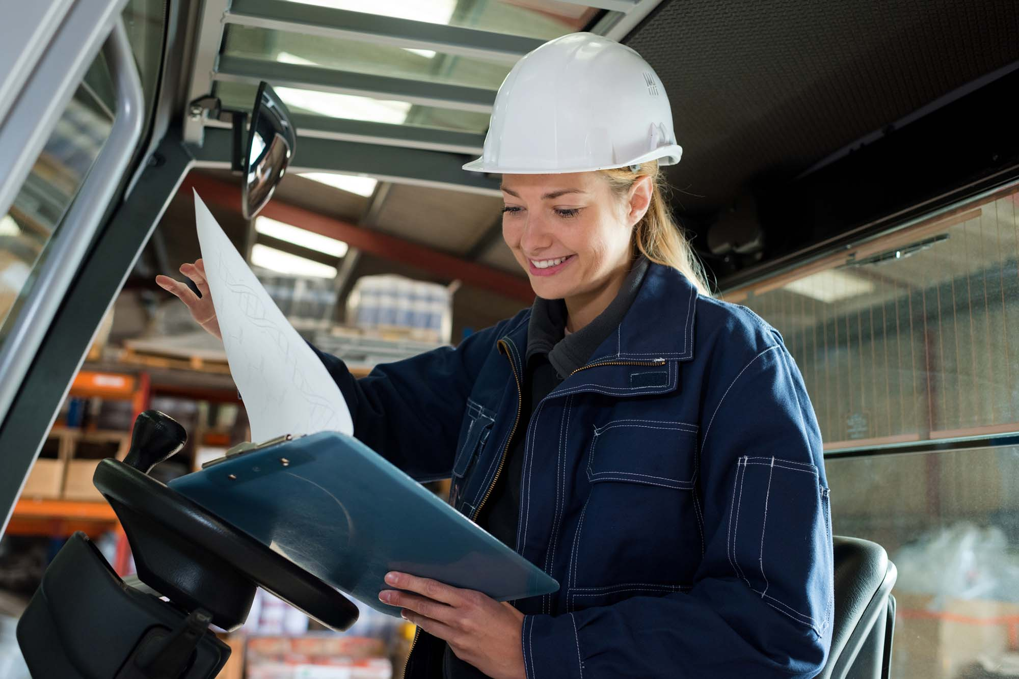 Woman looking a documents while using forklift